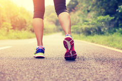 Fitness runner woman legs walking on trail Royalty Free Stock Images