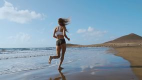Fitness Runner Woman Running On Beach Listening To Music