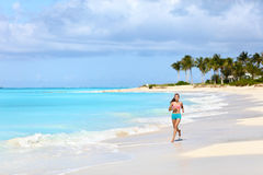 Fitness runner woman running on tropical beach. Fitness runner woman running on tropical white sand beach nature landscape outdoors. Beautiful nature in Royalty Free Stock Photo