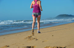 Fitness and running on beach, woman runner legs in shoes on sand near sea, healthy lifestyle and sport Stock Images