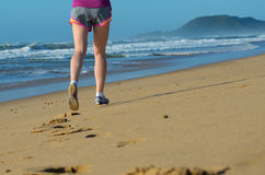 Fitness and running on beach, woman runner legs in shoes on sand near sea, healthy lifestyle and sport Royalty Free Stock Images