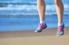 Fitness and running on beach, woman runner legs in shoes on sand near sea, healthy lifestyle and sport Royalty Free Stock Image