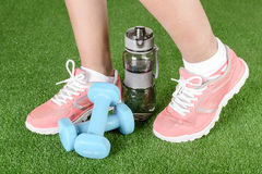 Fitness running shoes, outdoors. Fitness running shoes with a water bottle and dumbbells on a grass floor royalty free stock photo