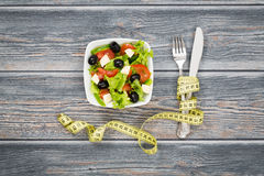 Fitness salad and measuring tape on wooden table. royalty free stock photo