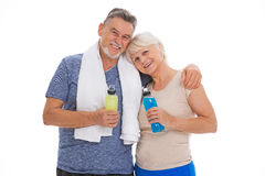 Fitness senior couple with towel and bottles. Senior couple standing over white background Stock Image
