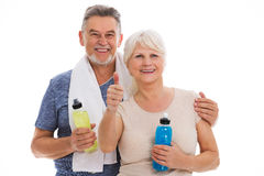 Fitness senior couple with towel and bottles. Senior couple standing over white background Royalty Free Stock Photography