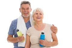 Fitness senior couple with towel and bottles. Senior couple standing over white background Stock Photography