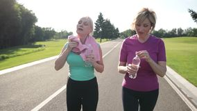 Fitness senior women drinking water after jogging stock footage