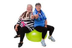 Fitness for senior women. Two senior women sitting on a fitness ball - isolated Royalty Free Stock Photography