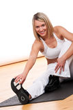 Fitness series - Blond woman exercising on mat. Blond woman in white outfit exercising on mat Stock Image