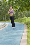 Fitness series jogging. An asian female striding along on the jogging path in a park Stock Photos
