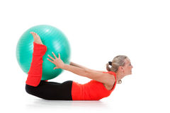 Fitness series: woman and exercise ball. Full body shot of a smiling woman lying down the floor and holding the pilates ball with her legs and hands . Orange Royalty Free Stock Photography