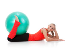 Fitness series: woman and exercise ball. Full body shot of a smiling woman lying down the floor and holding the pilates ball with her legs . Orange, green and Stock Photography