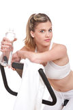 Fitness series - Woman with exercise bike. And bottle of water on white background Royalty Free Stock Photography
