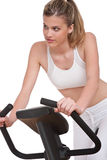 Fitness series - Young woman on exercise bike. On white background Stock Image