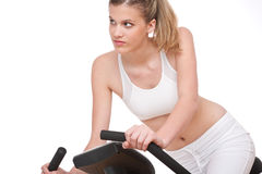 Fitness series - Young woman with exercise bike. On white background Royalty Free Stock Images