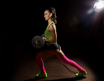 Fitness sexy girl with barbell on a dark background. Athlete doing exercises in the gym Royalty Free Stock Image