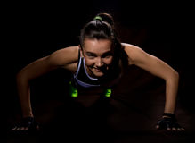Fitness sexy girl on a dark background. Athlete doing exercises in the gym Royalty Free Stock Photography