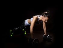 Fitness sexy girl on a dark background. Athlete doing exercises in the gym Royalty Free Stock Images