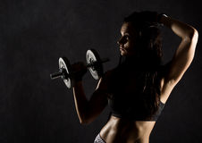 Fitness sexy girl with dumbbells on a dark background. Athlete doing exercises in the gym.  Stock Photography
