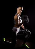 Fitness sexy girl with dumbbells on a dark background. Athlete doing exercises in the gym Royalty Free Stock Photos