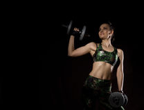 Fitness girl with dumbbells on a dark background. Athlete doing exercises in the gym. Free space for your text Stock Photography