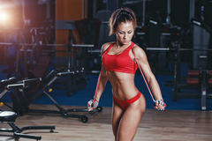 Fitness sexy girl with healthy sporty figure with skipping rope in gym Royalty Free Stock Images