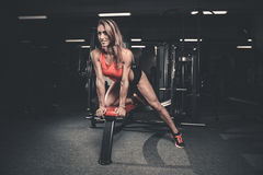 Fitness mode on diet with long female legs gym. Fitness mode on diet with long female legs in the gym royalty free stock photo