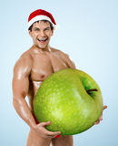 Fitness sexy Santa Claus on blue background, hold great green ap Stock Photos