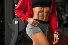 Fitness sexy woman showing abs and flat belly in gym. Beautiful athletic girl, shaped abdominal, slim waist Royalty Free Stock Image