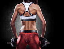 Fitness sexy woman on a sportswear in training pumping up muscle Stock Image