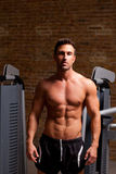 Fitness shaped muscle man posing on gym. Fitness shaped muscle man posing on dark gym Stock Photography