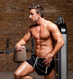 Fitness shaped muscle man posing on gym. Fitness shaped muscle man posing on dark gym Royalty Free Stock Photography