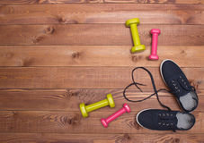 Fitness shoes with heart laces, weights on wooden background Stock Image