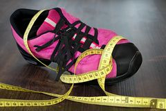 Fitness shoes and measuring tape on board. Workout as a healthy way of life. Shoes, measuring tape and board Stock Photos