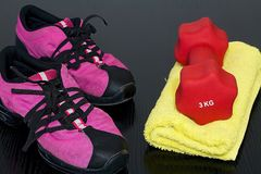 Fitness shoes and towel with dumbbell on board. Fitness shoes and towel with dumbbell ready for workout Royalty Free Stock Photography