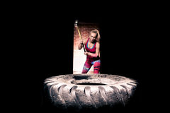 Fitness sledge hammer woman workout at gym.Sledgehammer tire hits woman workout at gym with hammer and tractor tire. Royalty Free Stock Image