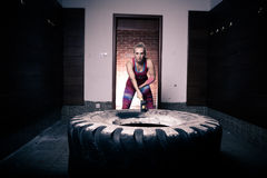 Fitness sledge hammer woman workout at gym.Sledgehammer tire hits woman workout at gym with hammer and tractor tire. Royalty Free Stock Photos