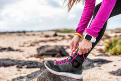 Fitness smartwatch woman runner getting run ready. Fitness smartwatch woman runner lacing running shoes on beach, Athlete girl getting ready for run workout royalty free stock photo