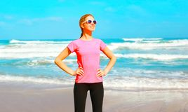 Fitness smiling woman on the beach near the sea Royalty Free Stock Images