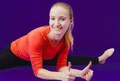On fitness Smiling woman showing a thumbs up sign on a blue background sitting on the splits. Looking at camera Stock Photos
