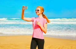 Fitness smiling woman takes a picture self portrait on a smartphone Royalty Free Stock Photo