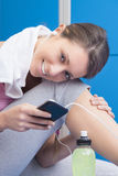 Fitness smiling woman using smart phone in dressing room Royalty Free Stock Photography