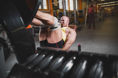 Fitness and Sport. Athletic man doing exercises on legs in gym among other people. Stock Photography