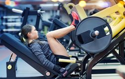 Woman flexing muscles on leg press machine in gym Royalty Free Stock Photography