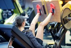 Woman flexing muscles on leg press machine in gym. Fitness, sport, bodybuilding, exercising and people concept - young woman flexing muscles on leg press machine Royalty Free Stock Image