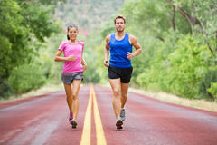 Fitness sport couple running jogging. Outside on road beautiful nature landscape. Runners training together for marathon run. Asian female sports women and fit stock images