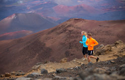 Fitness sport couple running jogging outside on trail. Fitness sport couple jogging outside, training together outdoors. Running on amazing trail at sunset Stock Image