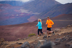 Fitness sport couple running jogging outside on trail. Fitness sport couple jogging outside, training together outdoors. Running on amazing trail at sunset Royalty Free Stock Photo