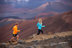 Fitness sport couple running jogging outside on trail. Fitness sport couple jogging outside, training together outdoors. Running on amazing trail at sunset Stock Photo